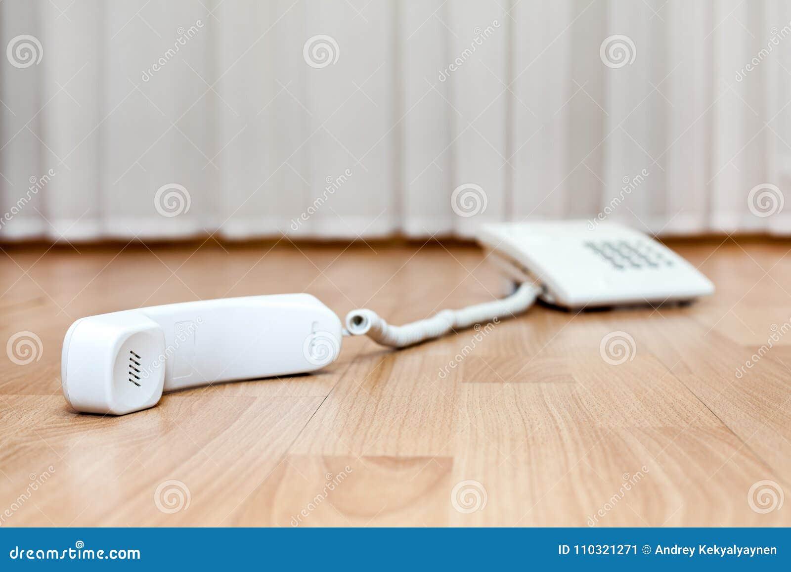 Weißes Telefon der Überlandleitung ist auf Boden mit fallengelassenem Hörer