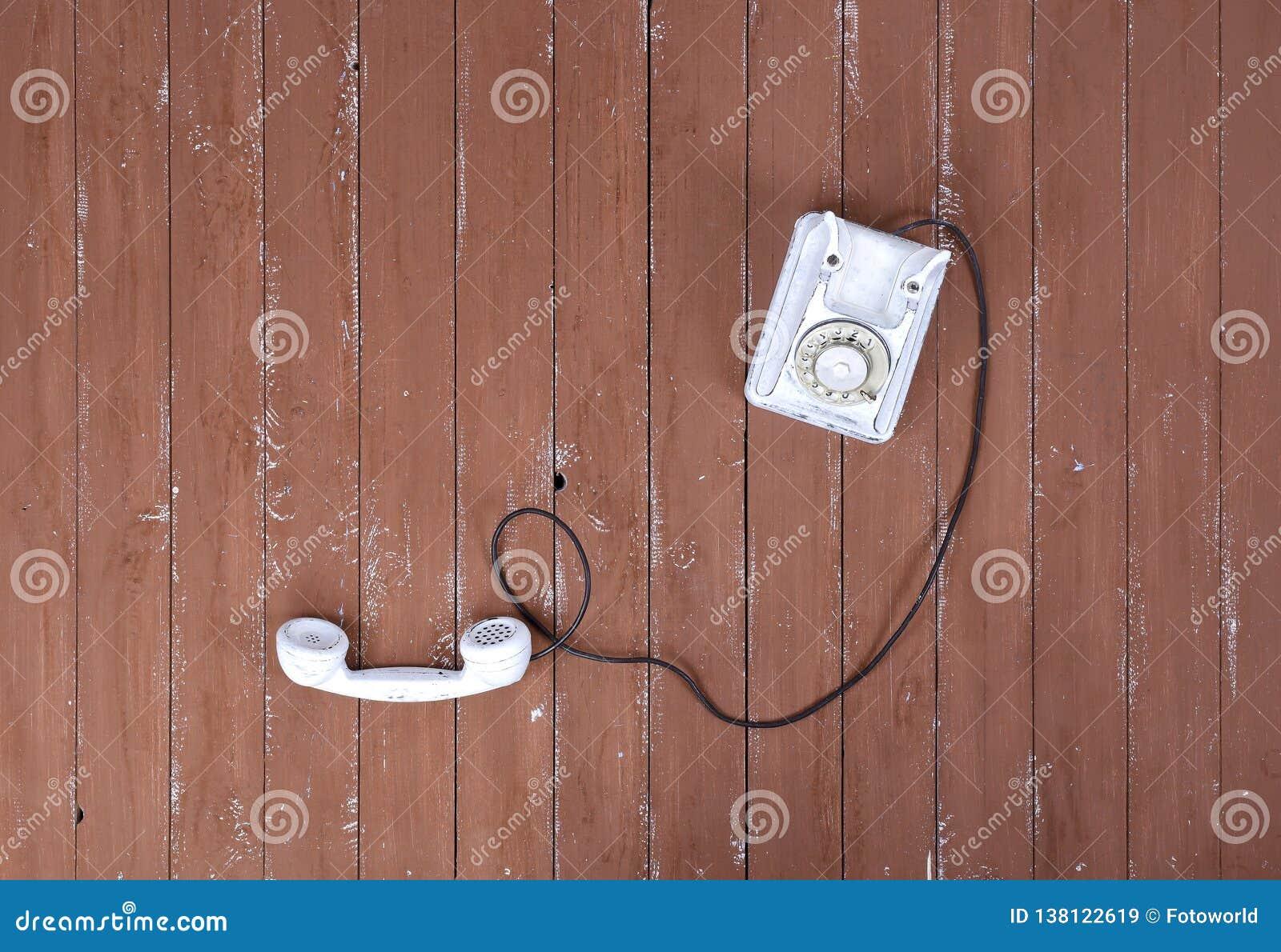 Weißes Weinlesetelefon der Draufsicht mit aufgenommen auf einem braunen Holz gemasert
