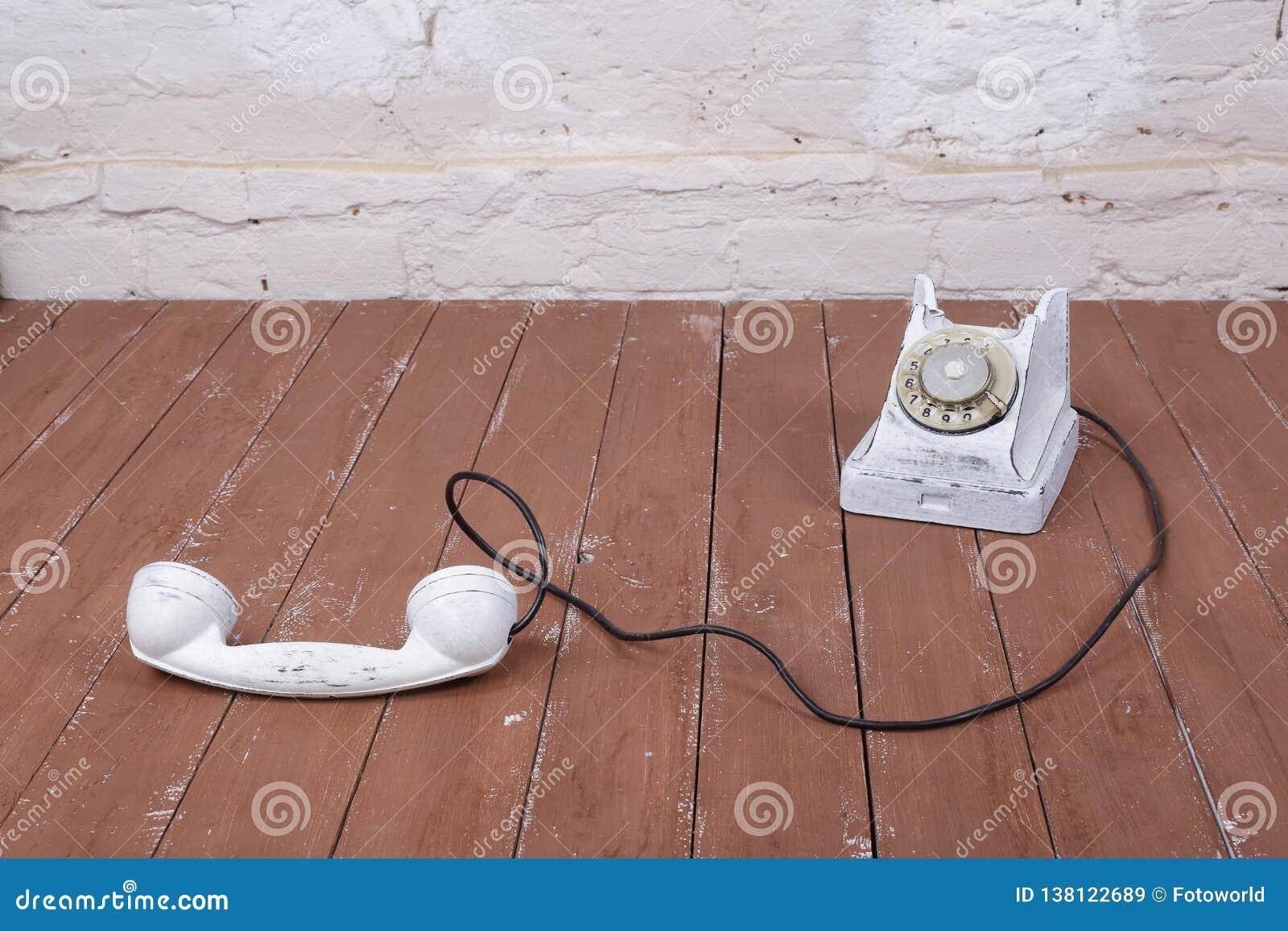 Weißes Weinlesetelefon mit aufgenommen auf einem hölzernen und weißen Wandhintergrund