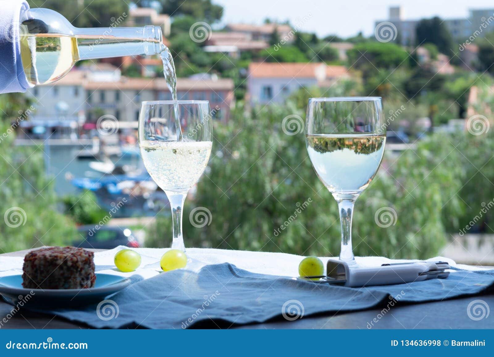 Weißwein von Provence, Frankreich, diente Kälte mit weichem Ziegenkäse auf Terrasse im Freien in zwei Weingläsern