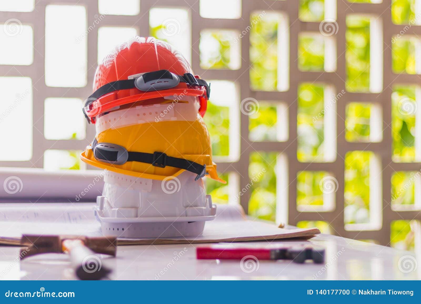 Weiße, gelbe und orange harte Sicherheit, Sturzhelmhut für Sicherheitsprojekt des Arbeiters oder Ingenieur auf Schreibtisch- und
