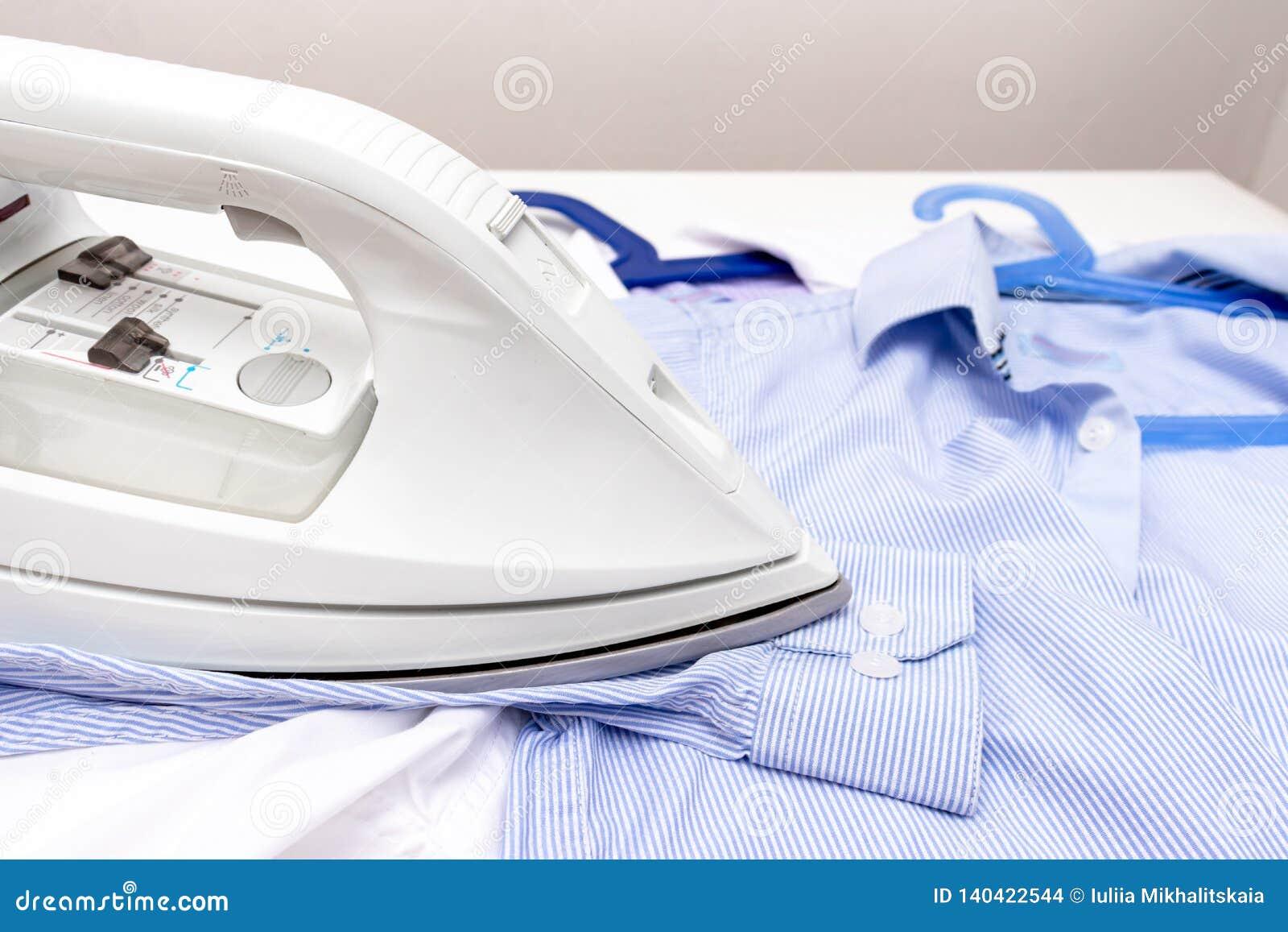 Weißer moderner elektrischer Eisenabschluß oben und blaue Hemden auf dem Tisch - Bügeln, Wäscherei und Hausarbeitkonzept