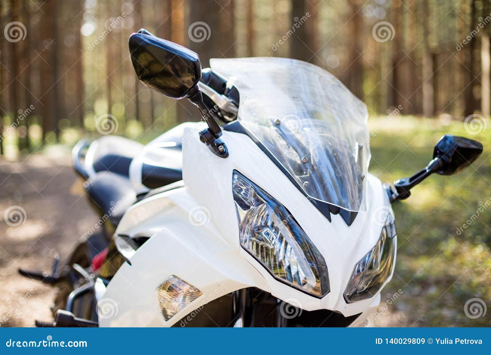 Weißes Motorrad, Lenkrad sonniges Wetter im Wald mit moto Tourismus und Erholungskonzept, Scheinwerfer von a