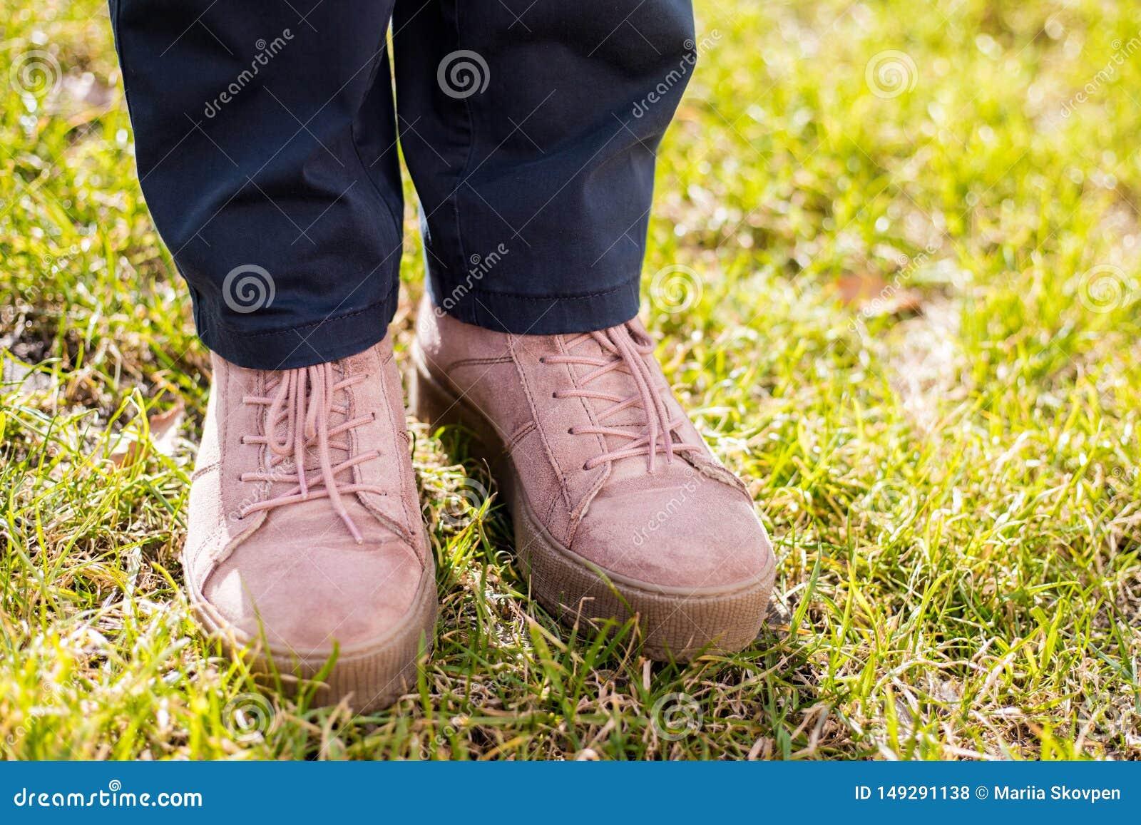 Weibliche Beine in den Jeans und in den rosa Turnschuhen auf gr?nem Gras, Fr?hlingstag