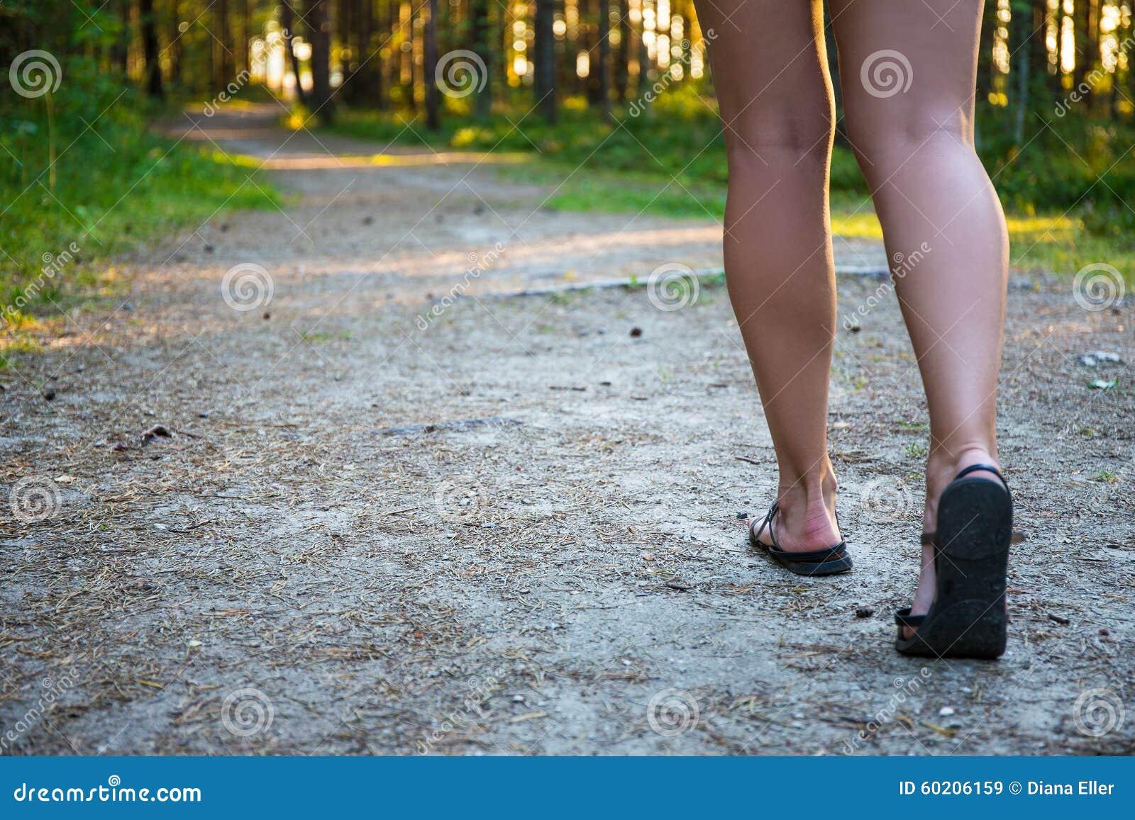 Weibliche Beine in den Sandalen, die auf Waldweg gehen