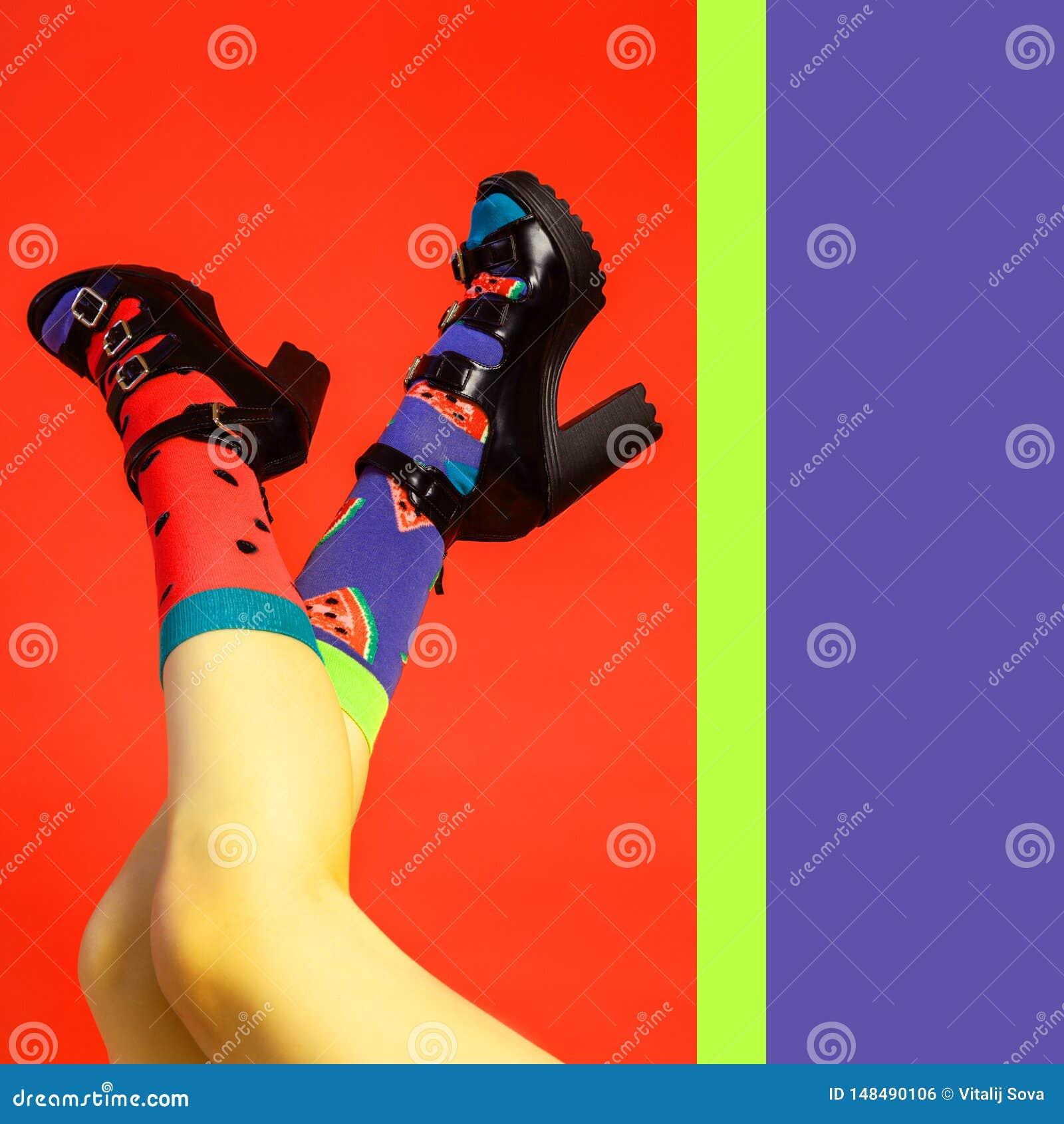 Weibliche Beine in den schwarzen Schuhen mit Fersen und hellen Farbsocken