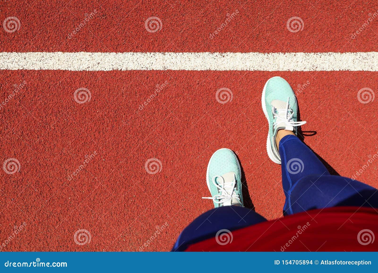 Weibliche Beine in den Turnschuhen auf rotem athletischem Bahnhintergrund