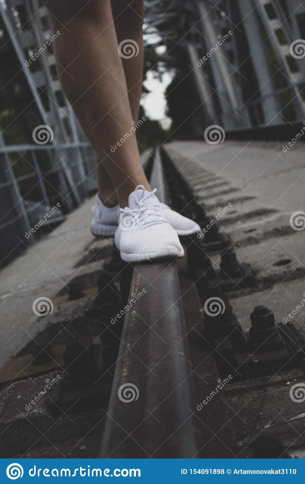 Weibliche Beine zu den Knien, in den weißen Turnschuhen, Stand auf den Schienen