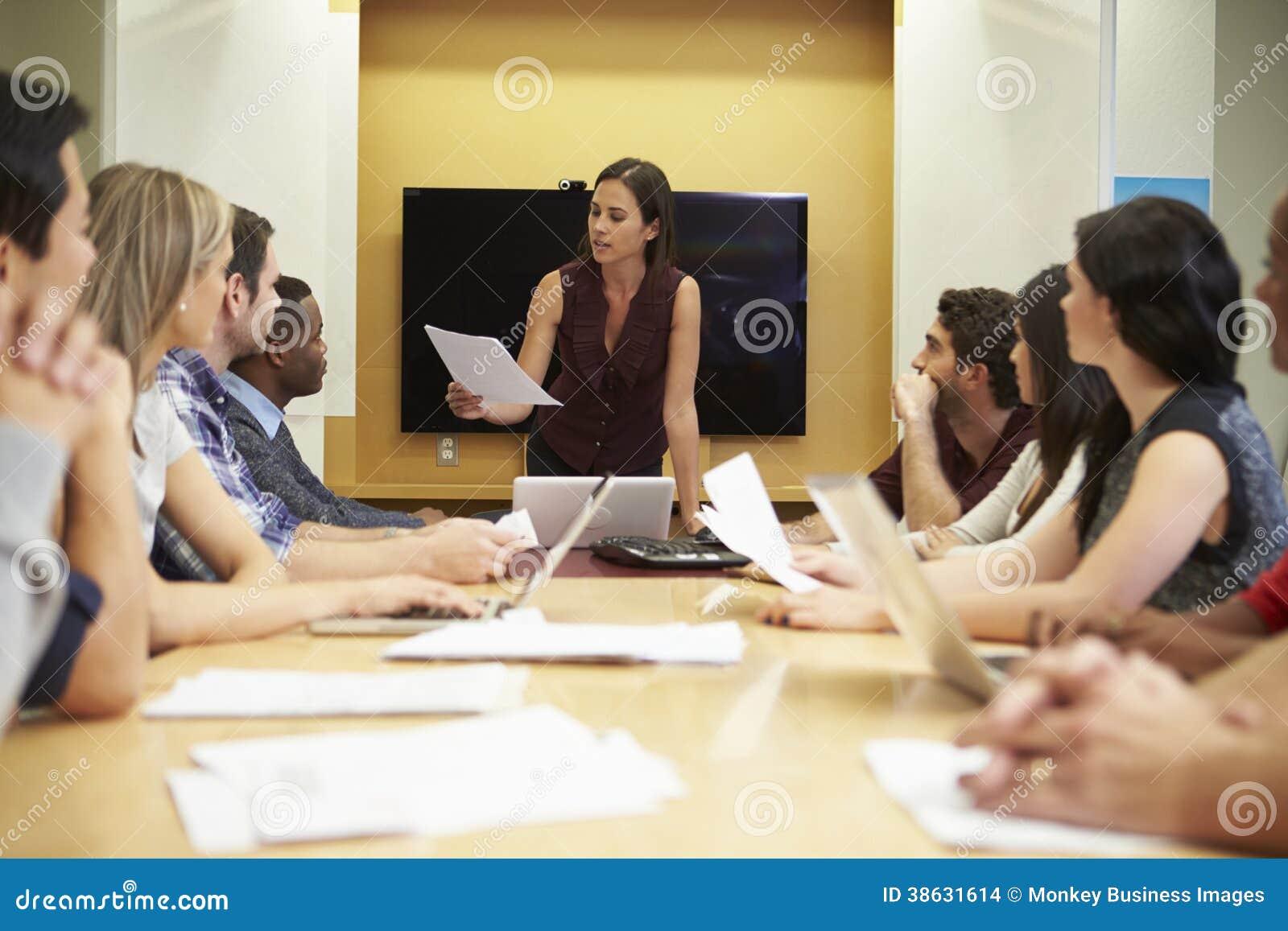 Weibliche Chef-Addressing Meeting Around-Sitzungssaal-Tabelle