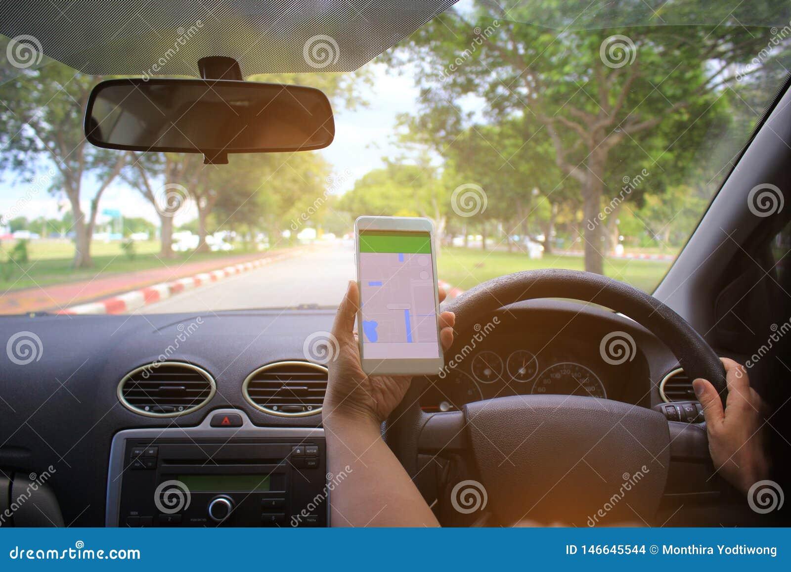 Weibliche Fahrerhände, welche auf der Autobahn die Autolenkplatte mit Karte gps-Navigationsanwendung halten