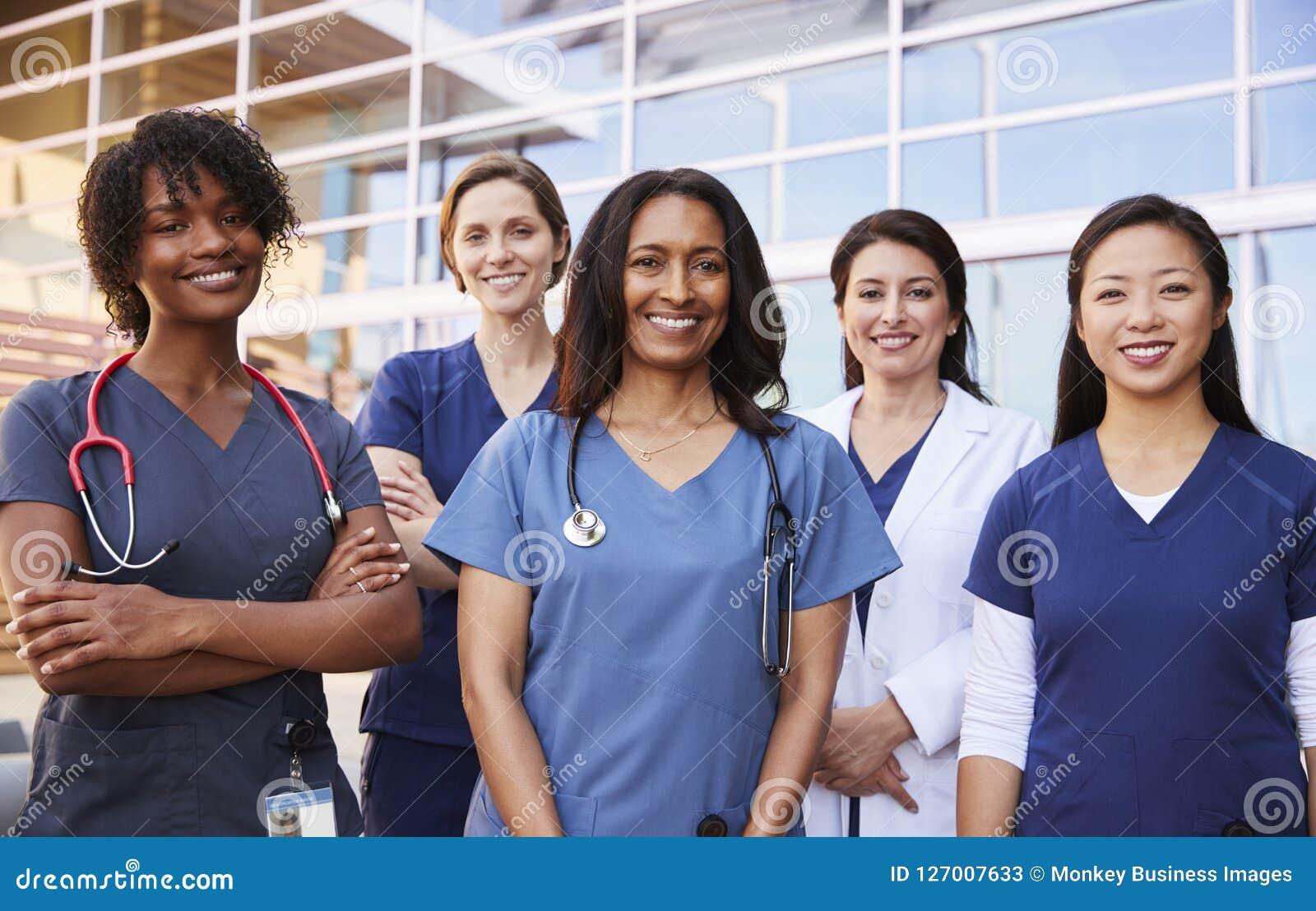 Weibliche Gesundheitswesenkollegen, die äußeres Krankenhaus stehen