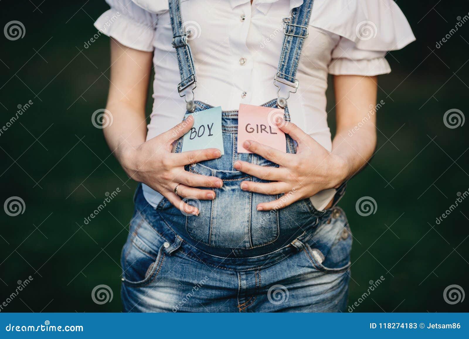 Weibliche Hände am Bauch mit mit JUNGEN- und MÄDCHEN-Karten