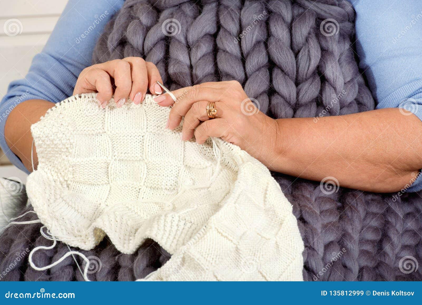 Weibliche Hände stricken eine Decke mit Stricknadeln liebhaberei
