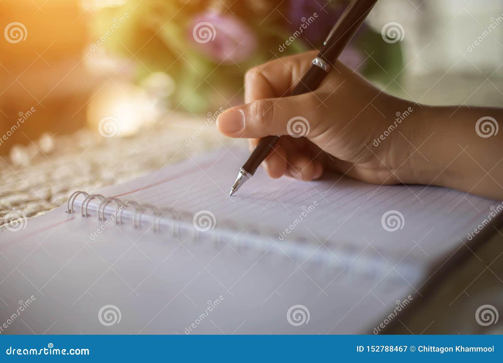 Weibliche H?nde mit Stiftschreiben auf Notizbuch