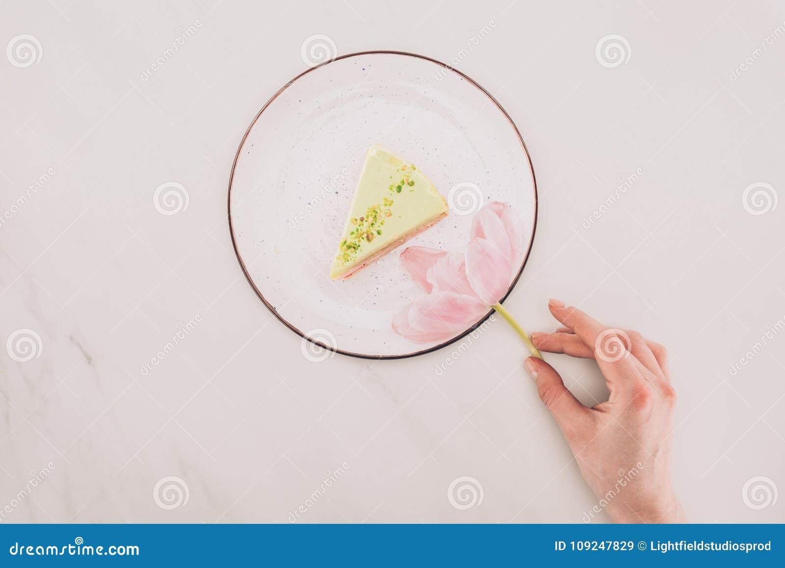 Weibliche Hand, Blume und Stück des Kuchens auf Platte auf weißer Tischplatte