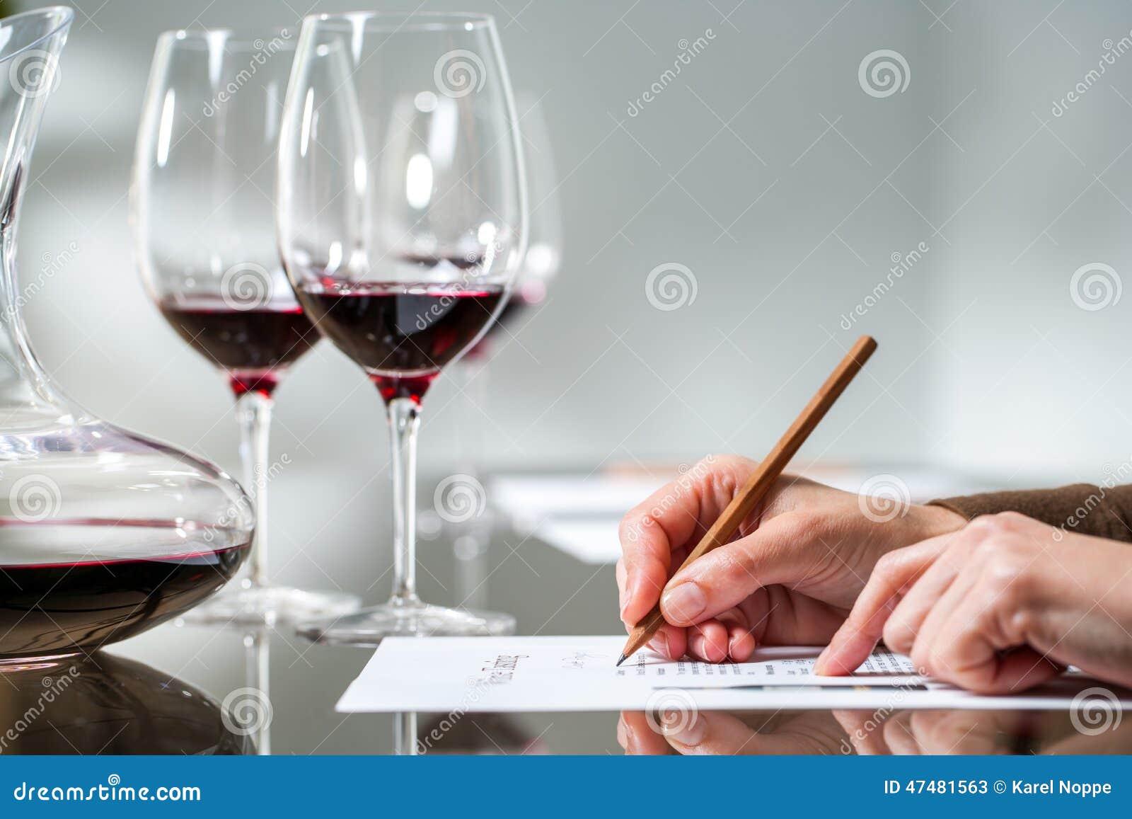 Weibliche Hand, die Kenntnisse an der roten Weinprobe nimmt