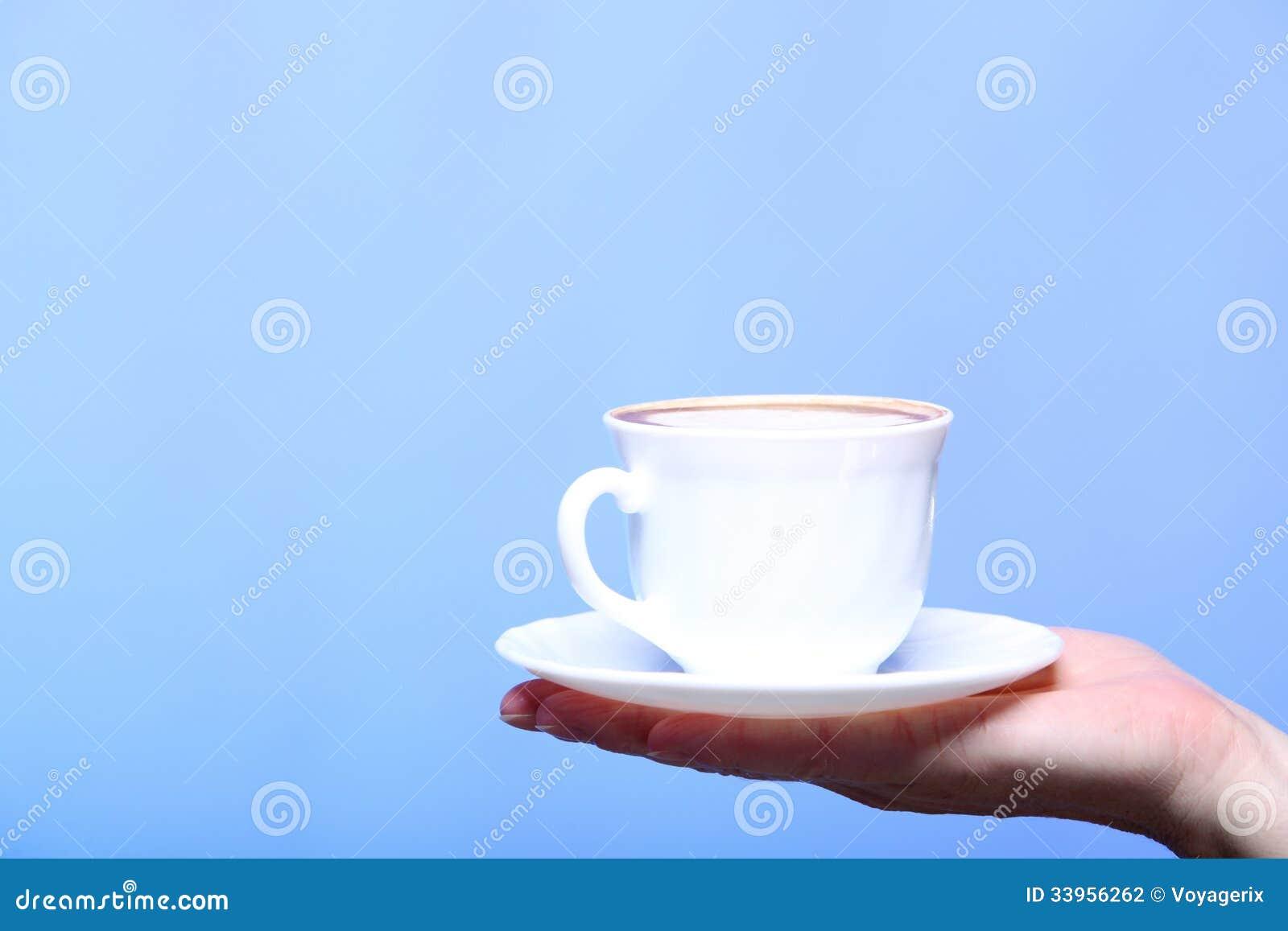 Weibliche Hand, die Schale heißen Lattekaffeecappuccino hält
