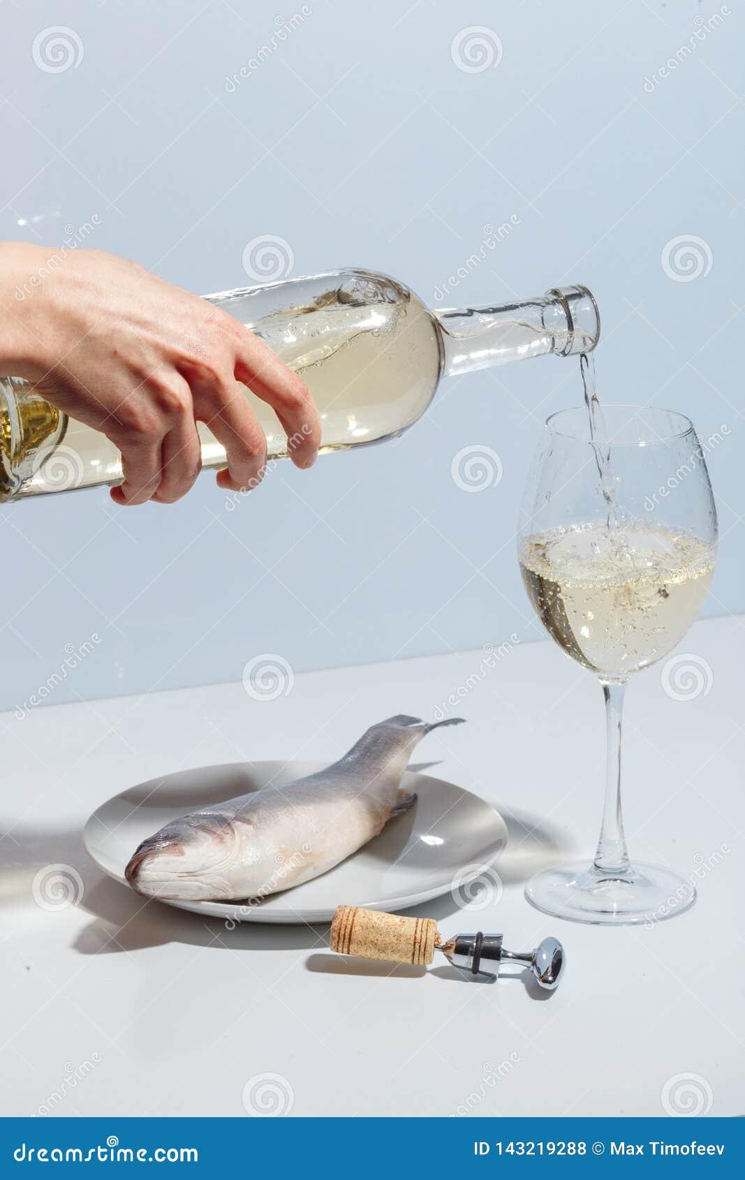 Weibliche Hand gießt Weißwein in ein Glas Kreatives Konzept Minimalistic