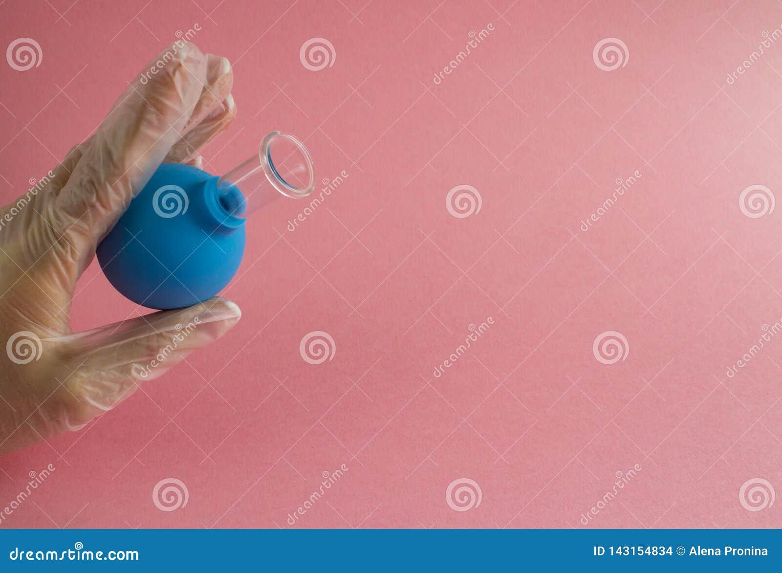 Weibliche Hand mit französischer Maniküre im Medizinhandschuh hält blaues kosmetisches medizinisches Glas für Vakuumgesichtsmassa