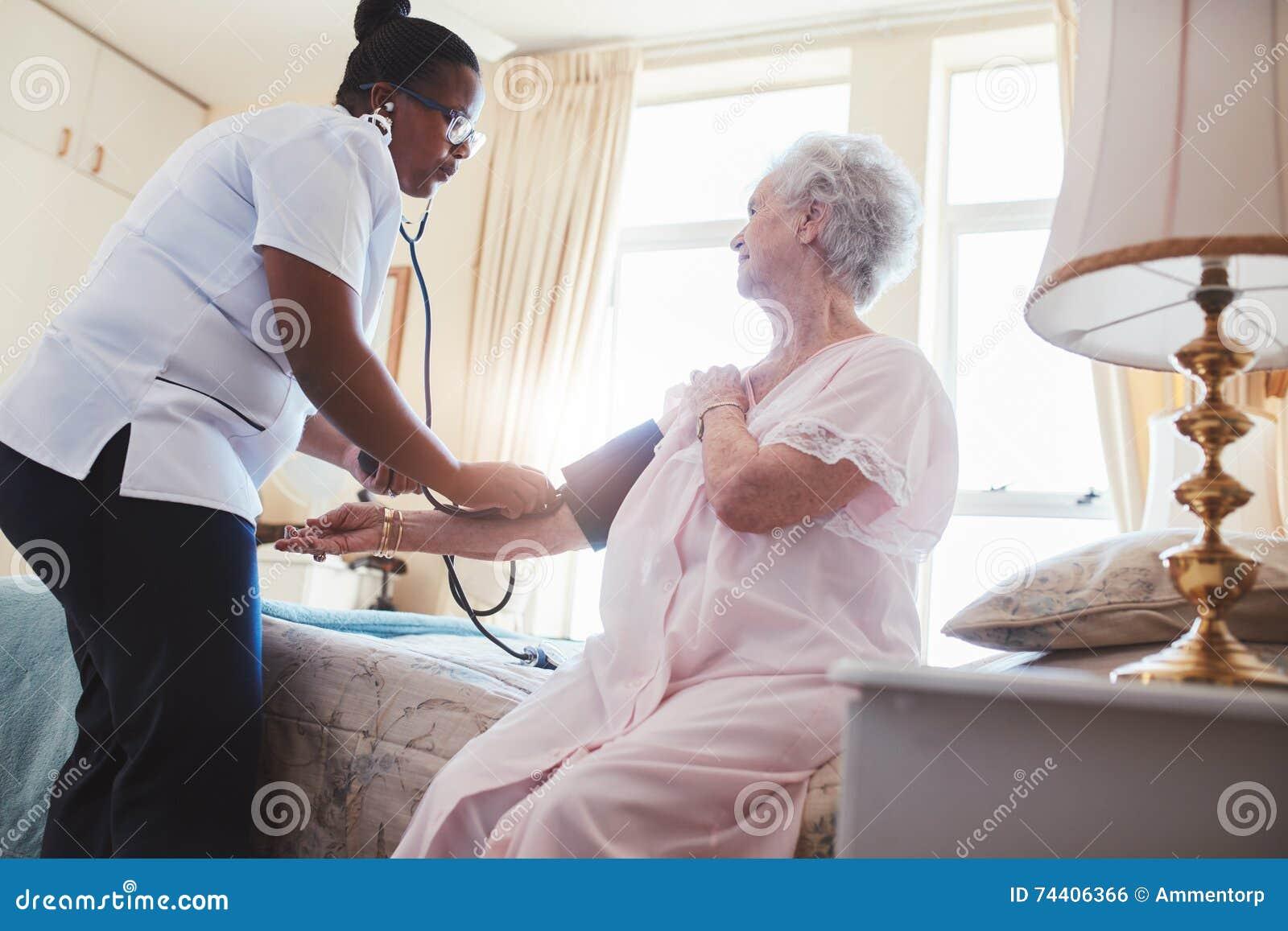 Weibliche Krankenschwester, die Blutdruck einer älteren Frau überprüft