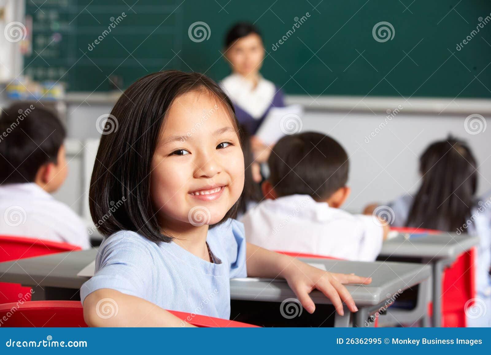 Weibliche Pupille, die am Schreibtisch in der chinesischen Schule arbeitet