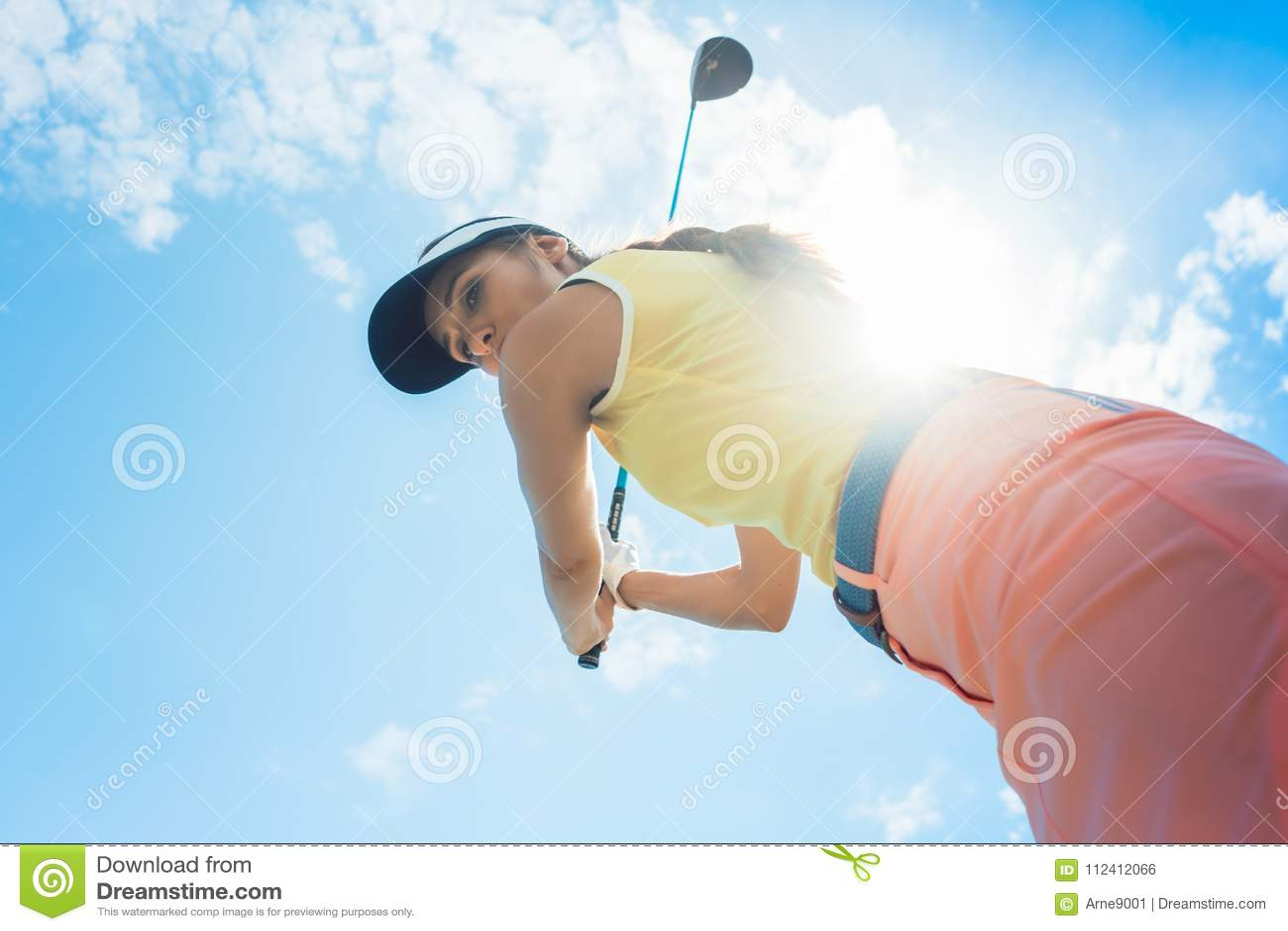Weiblicher Berufsspieler, der den Eisenclub beim Spielen des Golfs hält