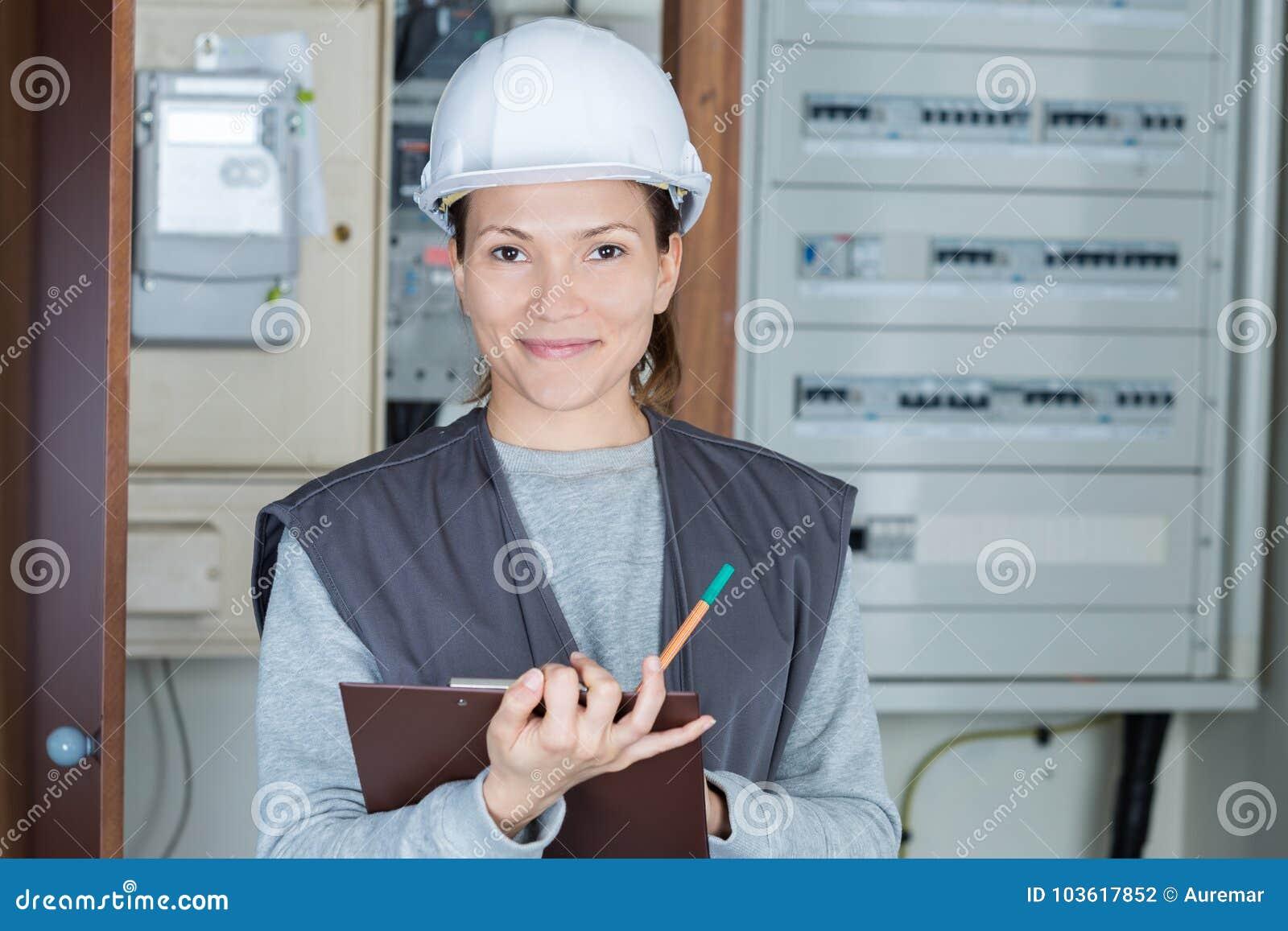 Weiblicher Elektriker des Porträts mit Klemmbrett am fusebox