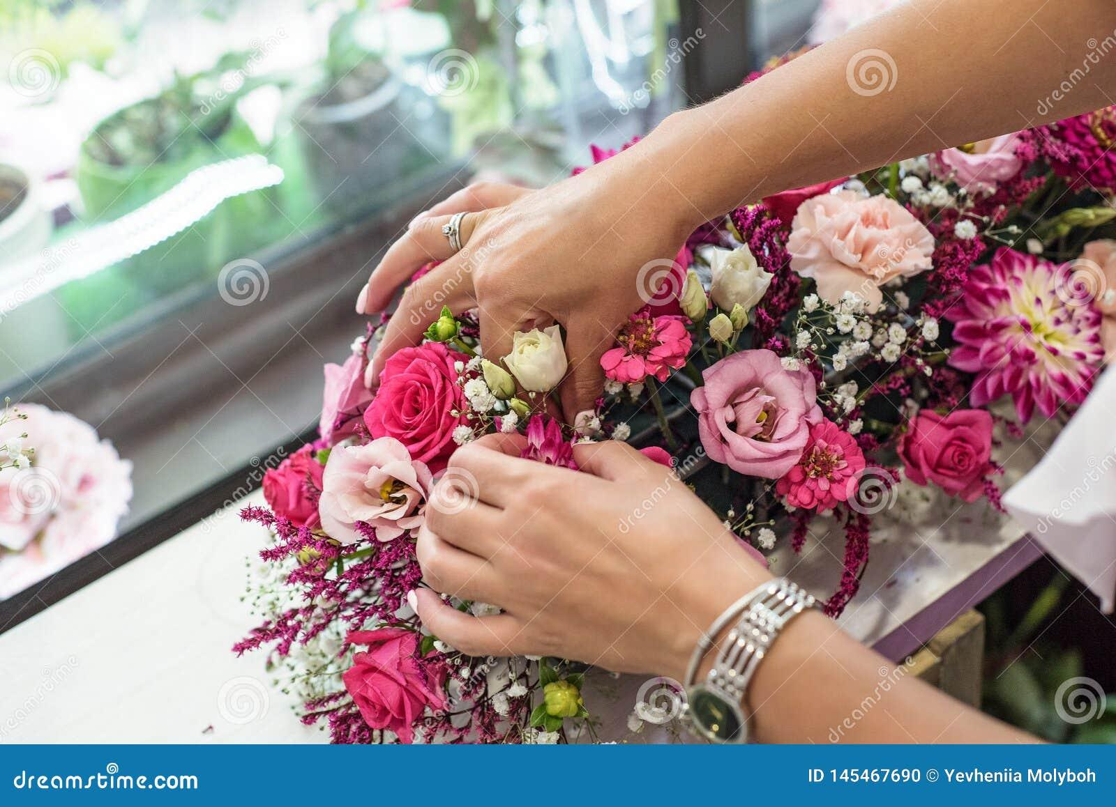 Weiblicher Florist, der sch?nen Blumenstrau? am Blumenladen macht