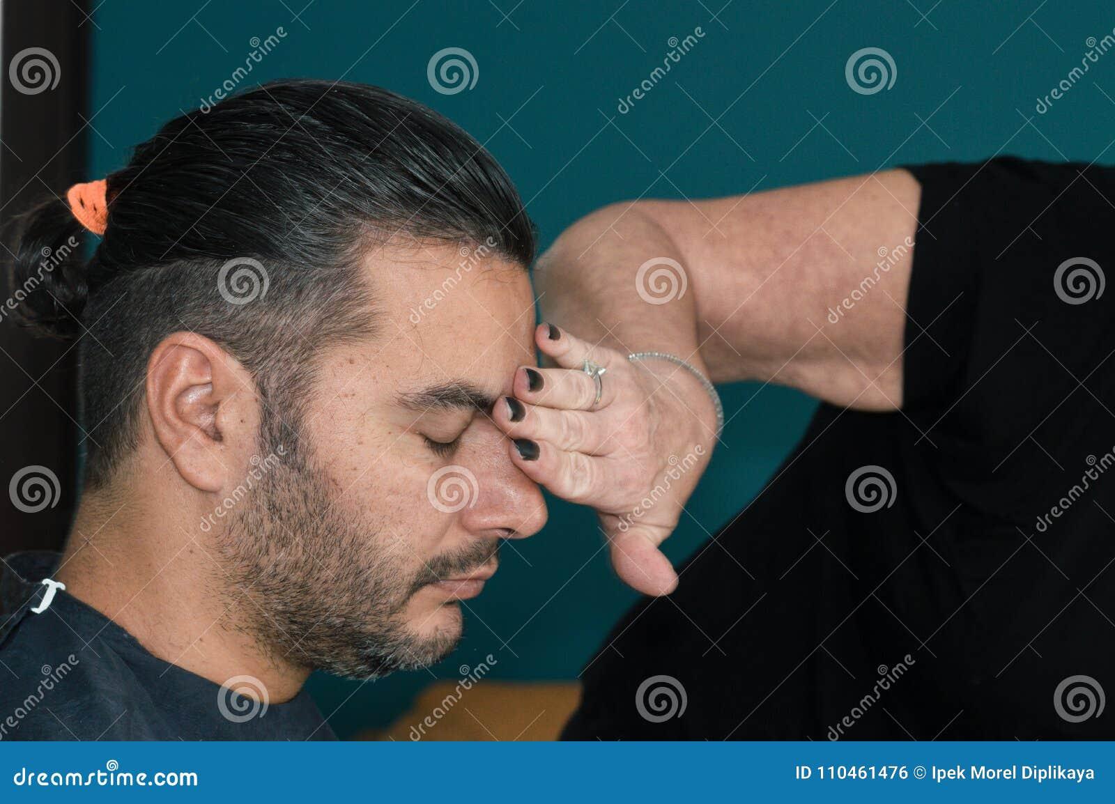 Weiblicher Friseur, der das Gesicht des jungen Mannes mit ihrer Hand säubert, nachdem sein Haar rasiert worden ist