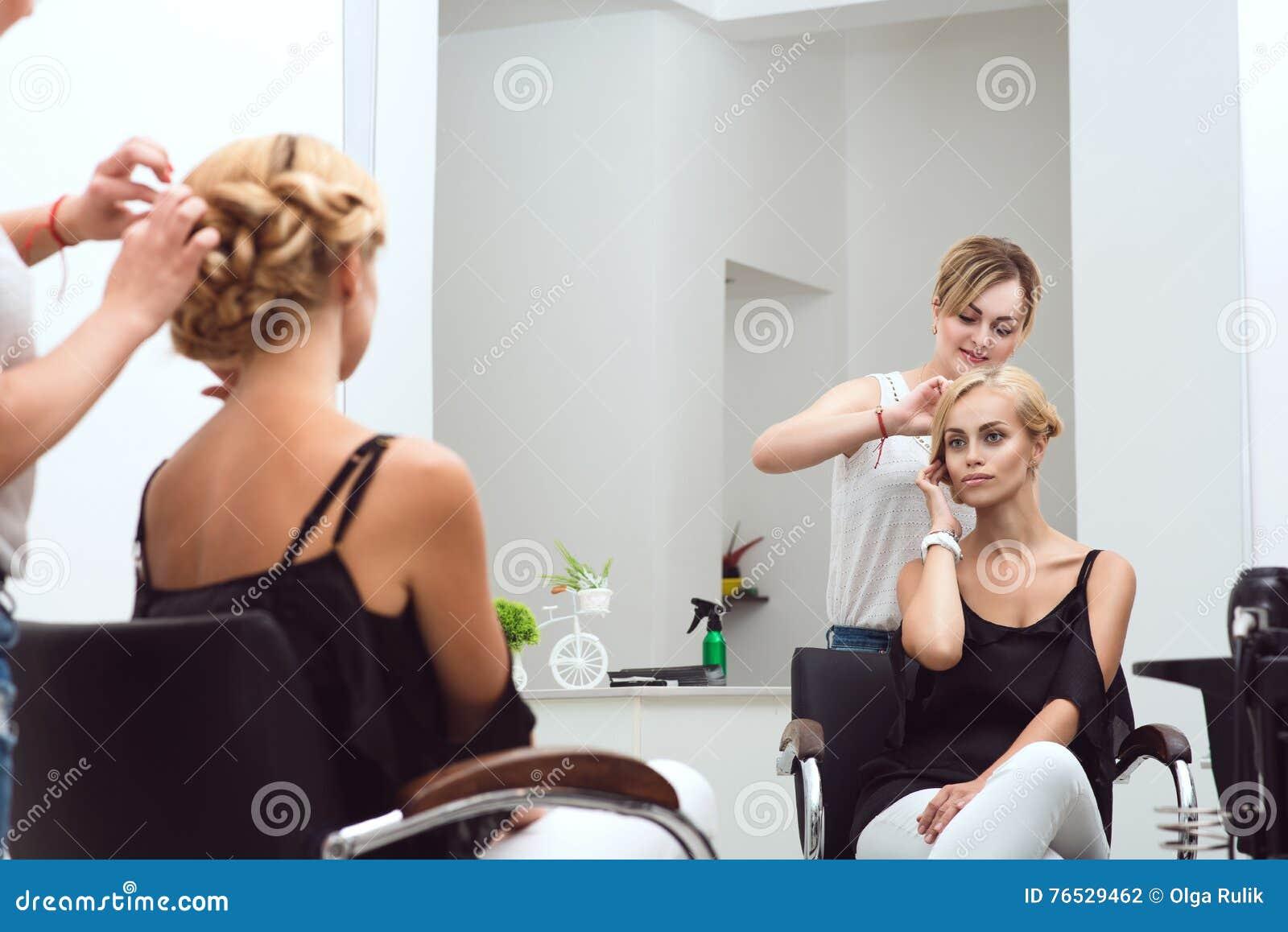 Weiblicher Friseur flicht ihr schönes client& x27; s-Haar am Schönheitssalon