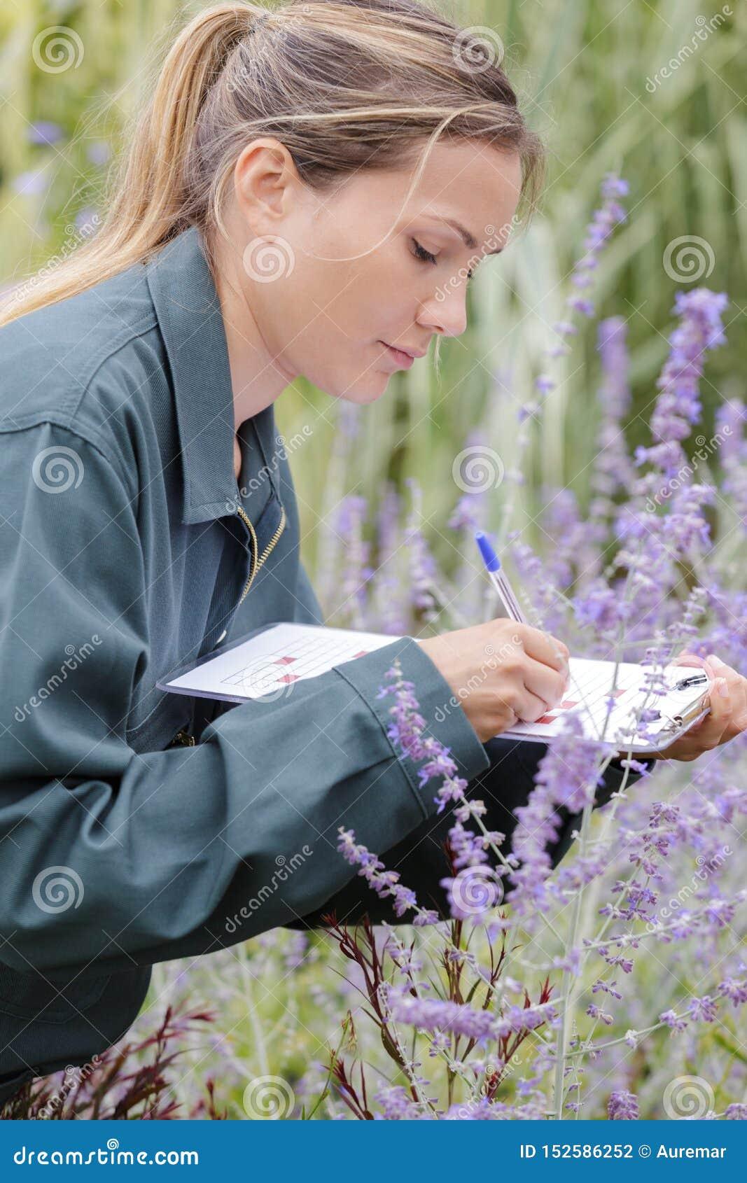 Weiblicher Gärtner, der Anmerkungen auf Klemmbrett macht