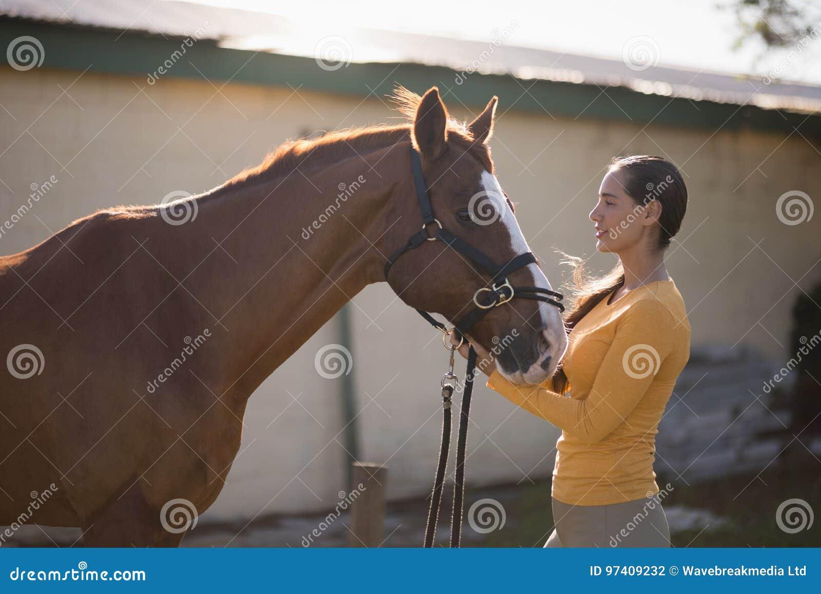 Weiblicher Jockey mit Pferd an der Scheune