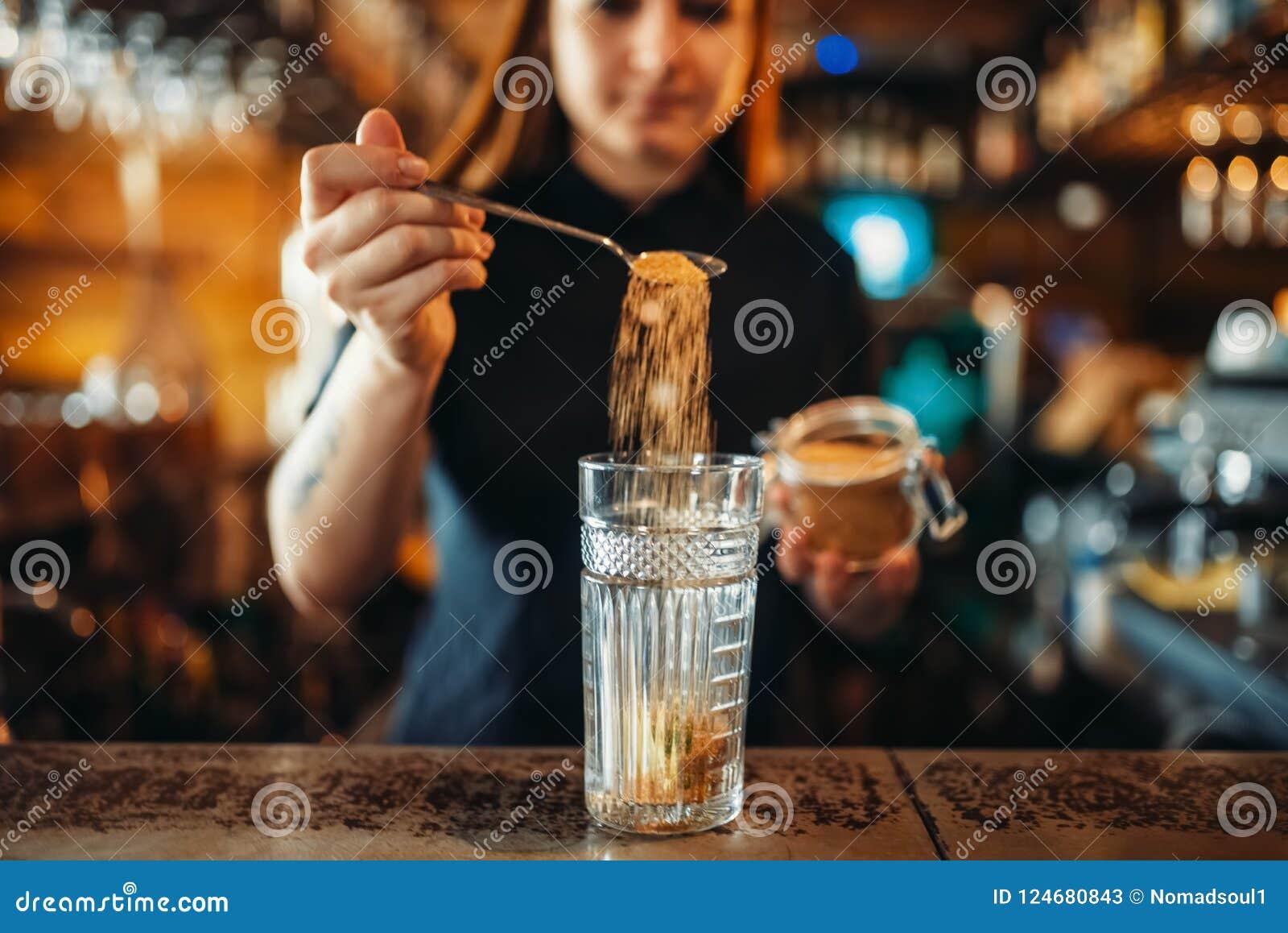 Weiblicher Kellner, der am Barzähler in der Kneipe mischt