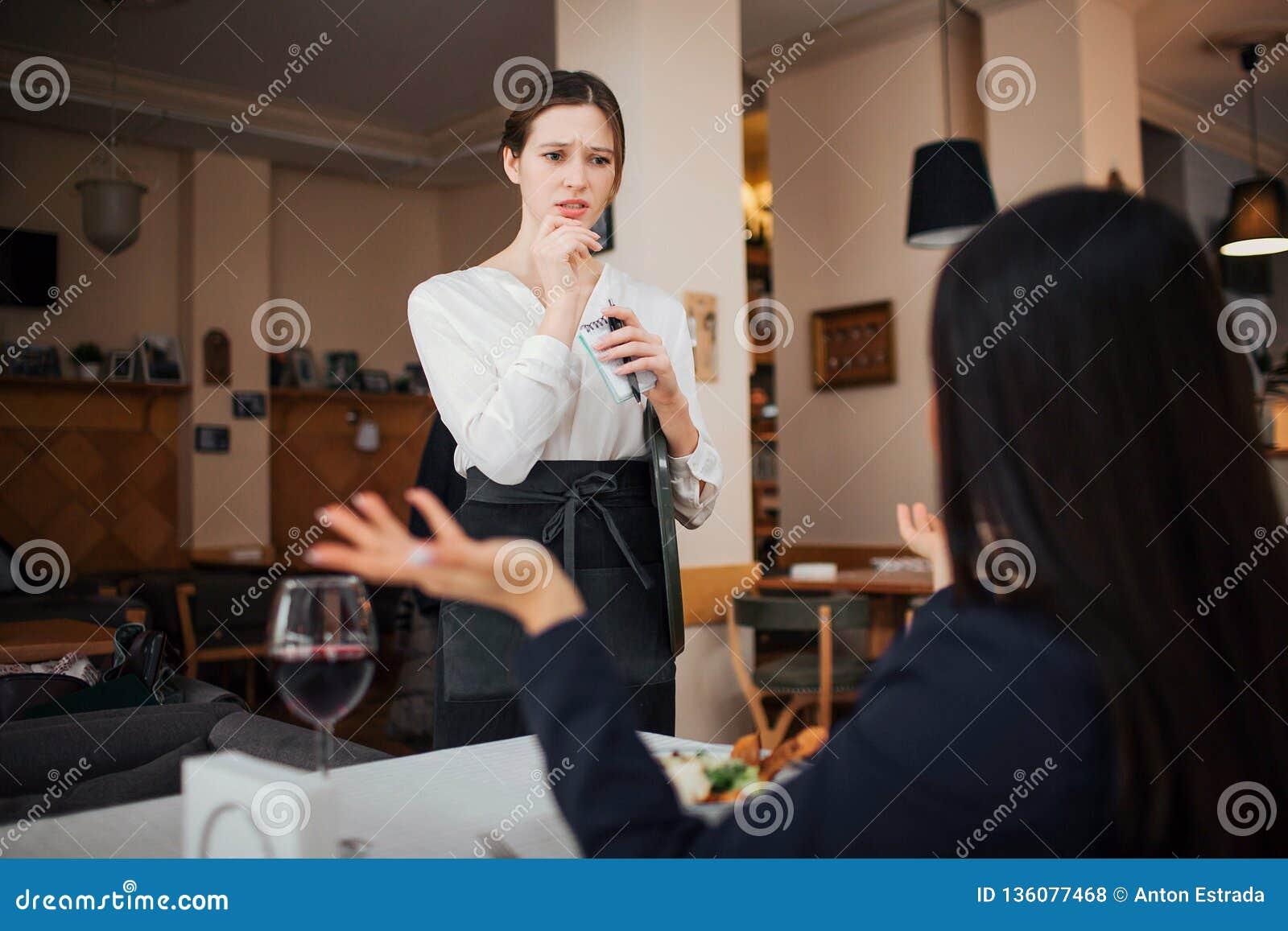 Weiblicher Kunde beschweren sich zur Kellnerin Sie hält Hände beiseite Kellnerin betrachten sie mit Interesse Sie steht bei Tisch