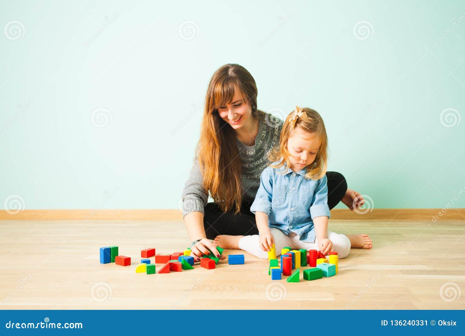 Weiblicher Lehrer und nettes Mädchen, die Sitzen auf einem Boden lernt
