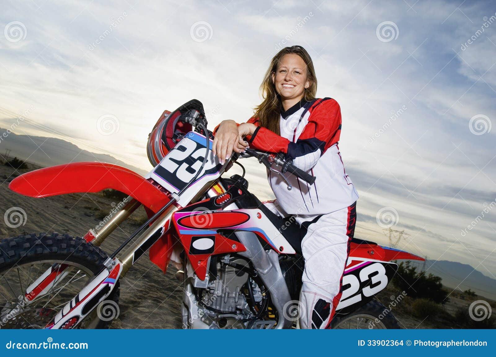 Weiblicher Rennläufer, der auf Motorrad gegen bewölkten Himmel sitzt