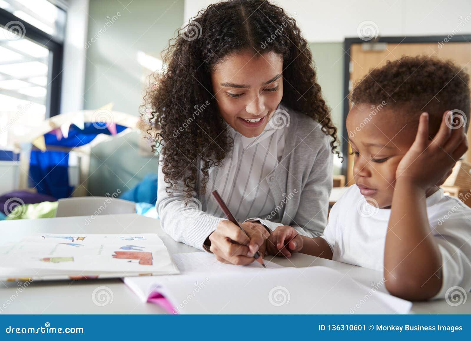 Weiblicher Säuglingsschullehrer, der ein auf einem mit einem jungen Schüler, sitzend an einem Tisch schreibend mit ihm, nah oben