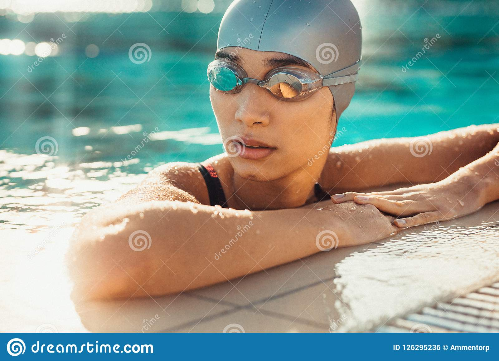 Weiblicher Schwimmer, der am Rand eines Swimmingpools sich entspannt