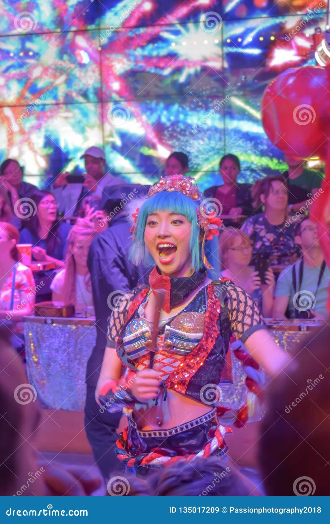 Weiblicher Tänzer, der herauf die Menge im Roboter-Restaurant zujubelt