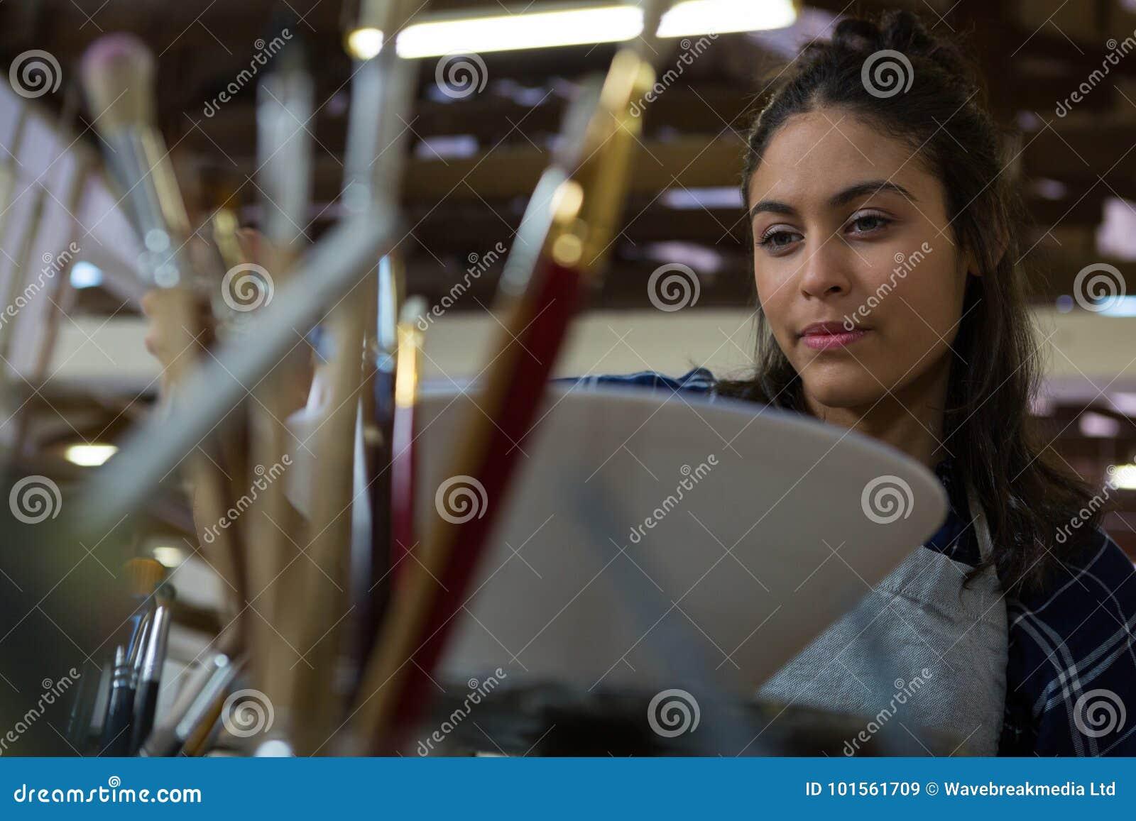 Weiblicher Töpfer, der eine Schüssel malt