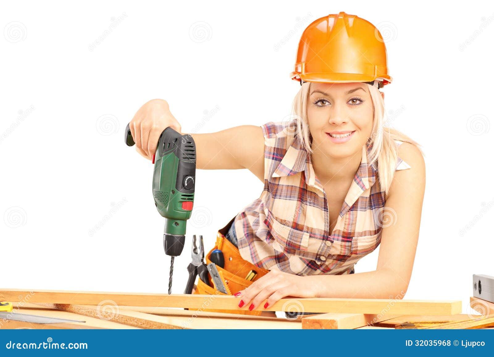 Weiblicher Tischler mit Sturzhelm bei der Arbeit unter Verwendung der Handbohrmaschine