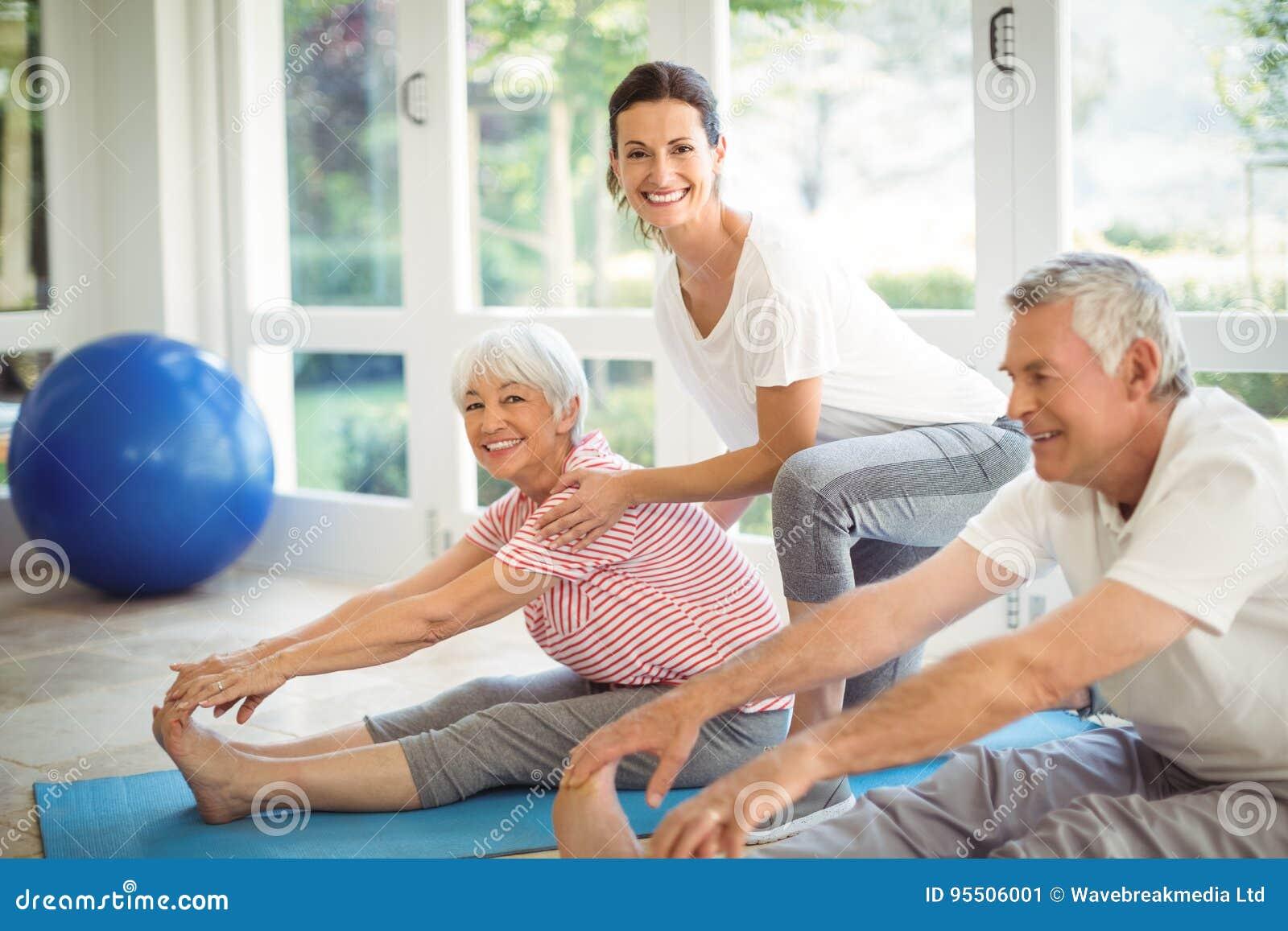 Weiblicher Trainer, der ältere Paare unterstützt, wenn Übung durchgeführt wird