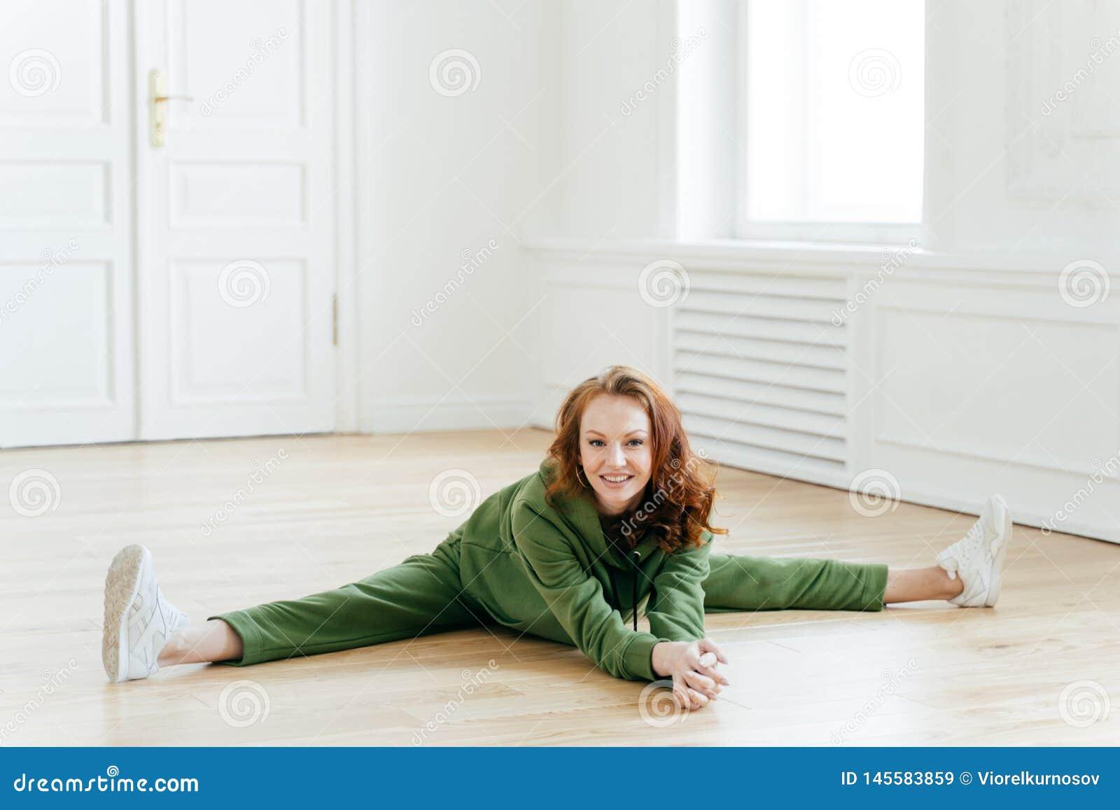 Weiblicher Turner in der Sportkleidung, tut Beinspalte, sitzt auf Boden, Haltungen im Yogaraum, hat Trainingsübungen, ausdehnt Be