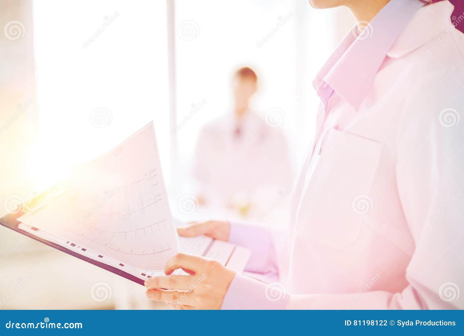 Weibliches haltenes Klemmbrett mit Kardiogramm