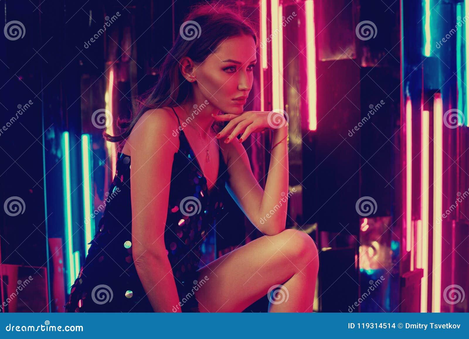 Weibliches Modell in schwarzem glänzendem cami Kleid, das auf großem Würfel sitzt und