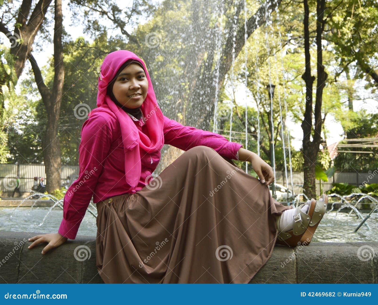 Weibliches moslemisches Sitzen auf Brunnen