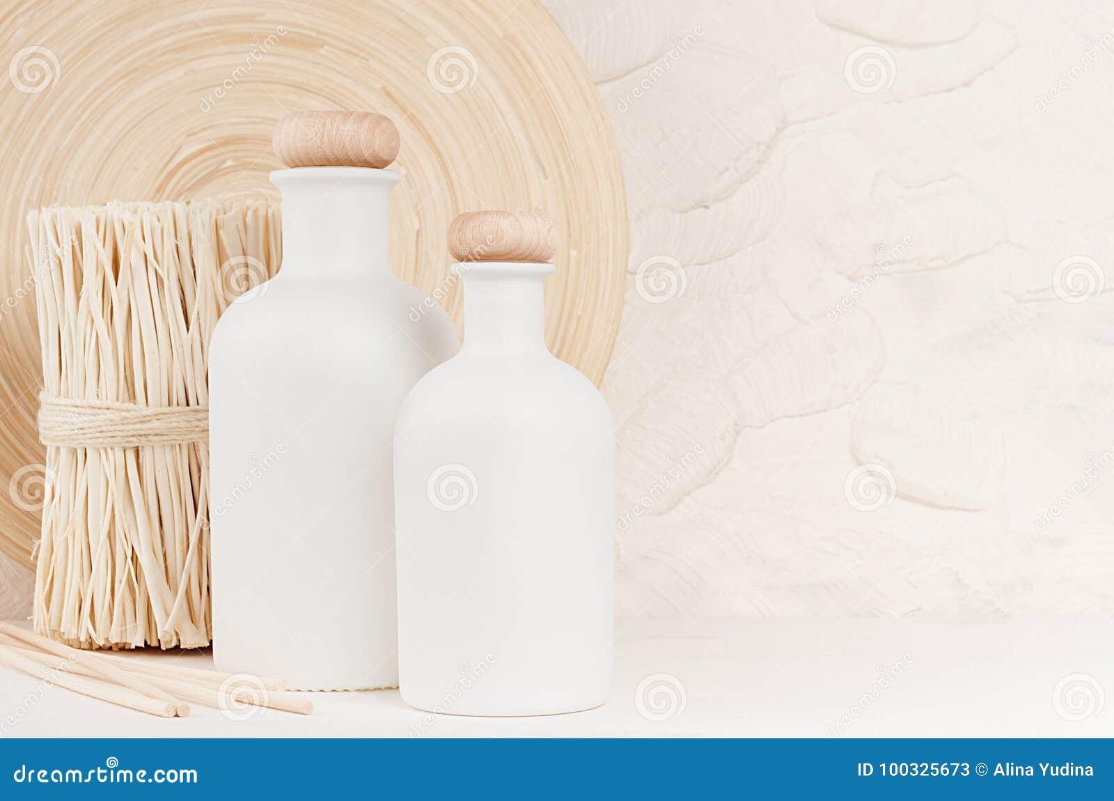 Weicher eleganter Hauptdekor mit weißen Flaschen und den beige Zweigen auf weißem hölzernem Brett