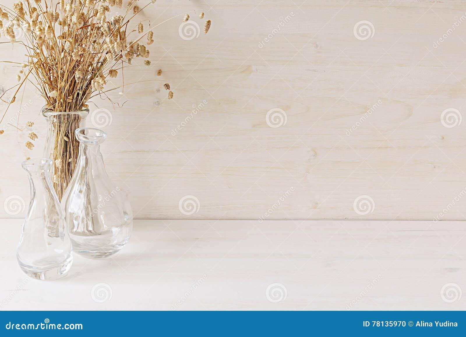 Weicher Hauptdekor des Glasvase mit den Ährchen auf weißem hölzernem Hintergrund