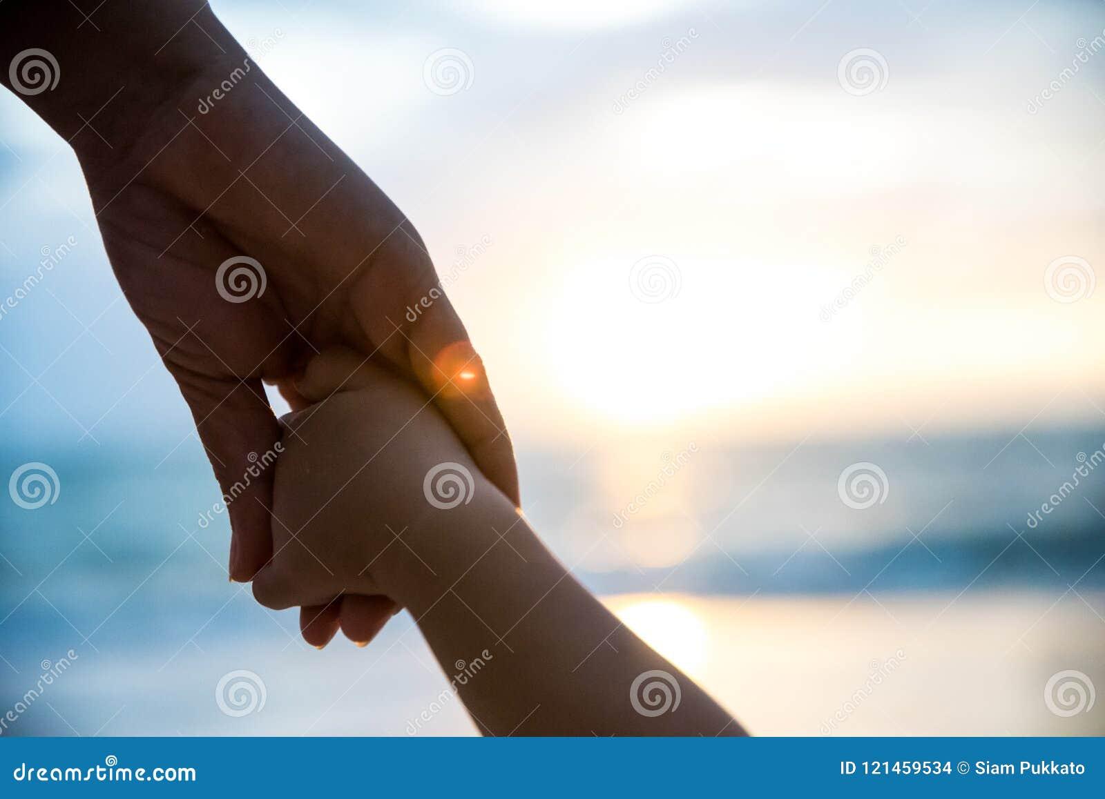 Weichzeichnungselternteilgriff die kleines Kinderhand während des Sonnenuntergangs