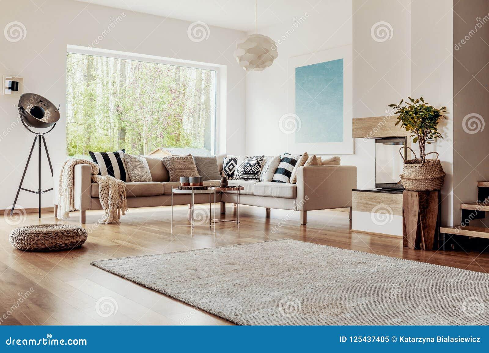 Weidenosmane und eine industrielle Stehlampe in einem hellen Wohnzimmerinnenraum mit schickem Dekor und hölzernen Elementen